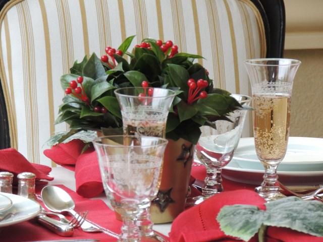 Mesa montada com porcelanas , pratarias e copos. O jogo americano na cor vermelha, e guardanapos vermelhos com prendedor em forma de folhagem, ao centro pequeno vaso com folhagem verde com alguns brotos em vermelho, logo a frente copos de champanhe e copo de água, o