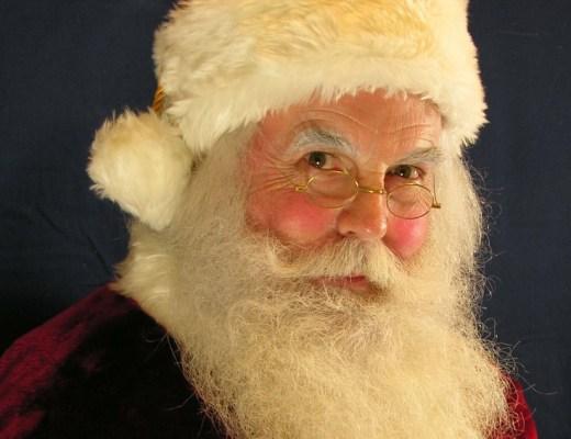 Imagem do rosto do Papai Noel, velho senhor com faces rosadas, grande barba branca, óculos e um gorro vermelho com a faixa branca de algodão.