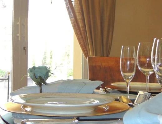 mesa redonda de madeira, junto a uma porta de vidro, com cortinas marrom, o tampo de vidro sobre a mesa, protege o souplat na cor dourada sobre ele um prato de porcelana branca com as bordas em detalhes listrados em verde e ouro, o guardanapo branco está com um porta-guardanapo em formato de rosa azul, o jogo americano redondo, é da cor branca. A frente de cada prato, as taças de vinho e champanhe vazias e o copo de água. Aparece apenas uma faca em prata junto ao lado esquerdo do prato.