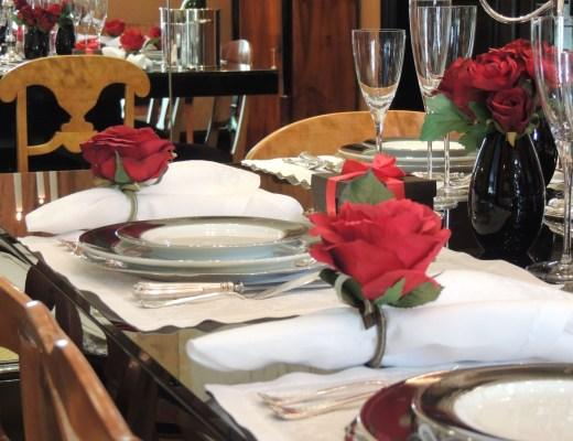 Mesa retangular ,em madeira escura, com decoração de natal, com dois candelabros , um em cada lateral da mesa, temos 3 posições de cada lado e um em cada ponta da mesa, os arranjos florais em vermelho estão no centro da mesa, o jogo americano é em tecido branco com suaves bordados, o porta guardanapo é um rosa vermelha, os guardanapos brancos da cor do jogo americano, as porcelanas schmidt - modelo Royal, brancos com bordas preta com detalhes em prata. em cada posição temos um copo de vinho branco, copo de água e uma taça de champanhe.