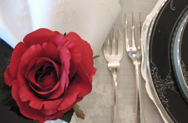 mesa de madeira retangular na cor preta, montada para oito lugares, ao centro dois castiçais com velas brancas, nos lugares jogo americano em linho branco com detalhes bordados, pratos em porcelana branca com as bordas na cor preta, os talheres em cada lugar com faca de peixe e faca a direita, garfo de peixe e garfo a esquerda, os talheres de sobremesa acima dos pratos, guardanapos em tecido de linho branco, adornados com porta guardanapos em forma de rosa vermelha, ainda no centro da centro conjunto de pequenos vasos com flores vermelhas