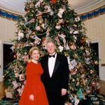 Presidente Bill Clinton e sua esposa Hilary Clinton, a frente de enorme árvore de natal com muitos enfeites. Ele usa um smoking (terno preto , camisa branca e gravata borboleta preta) e a esquerda está sua esposa usando um lindo vestido longo, na cor vermelha, com mangas cumpridas e decote careca. Eles estão no Salão Nobre da Casa Branca, sede do governo americano.