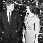 imagem em preto e branco, do Casal JFK, John Kennedy, usando terno escuro, camisa branca e gravata escura e Jackie , que usa um conjunto com golas grandes entrelaçadas, os dois estão se olhando, a frente de uma enorme árvore de natal, com muitos enfeites. Tudo isso no salão nobre da Casa Branca, sede do governo americano.