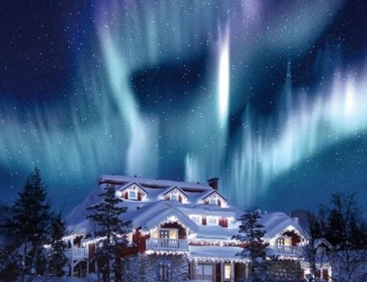 Foto noturna, de uma casa de vários andares na neve. Telhados e tudo que a rodeia está branco com a neve. Ao fundo o céu escuro é iluminado por um impressionante clarão verde e violeta de intensidade fulgurante - a famosa aurora boreal.