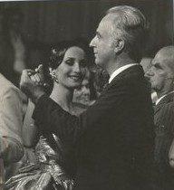 """retrato em preto e branco, de Claudia Matarazzo aos 26 anos de idade vestida com um longo rodado e dourado, valsando com seu pai - um senhor de terno escuro e cabelos prateados. O retrato foi tirado na gravação do programa """"Festa Baile"""""""