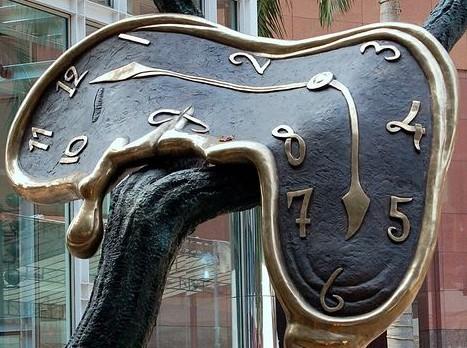 Escultura de um Relógio, em bronze, fundo azul escuro e borda e ponteiros na cor de bronze claro, a peça está sobre um tronco em bronze, simbolizando um galho de árvore, e o relógio está maleável sobre o tronco, marca seis horas.