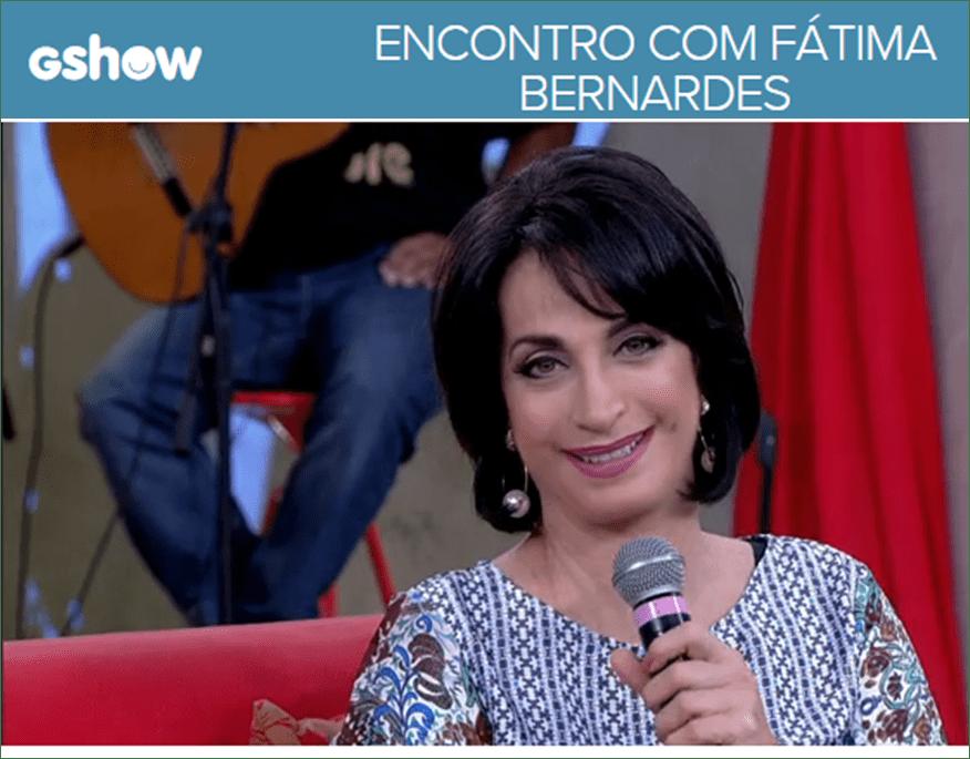 Claudia Matarazzo no programa Encontro com Fátima Bernardes, sentada no sofá em tom de vermelho, ela veste um blusa na cor azul acinzentado com pequenos detalhes, florzinhas, ela está com o microfone na mão direita, a frente junto a região do pescoço.