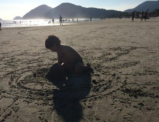 Num dia de sol, criança pequena, brinca na praia, fazendo montes de areia. Ele aparece em primeiro plano e ao fundo , muito longe, algumas outras pessoas transitam na praia.