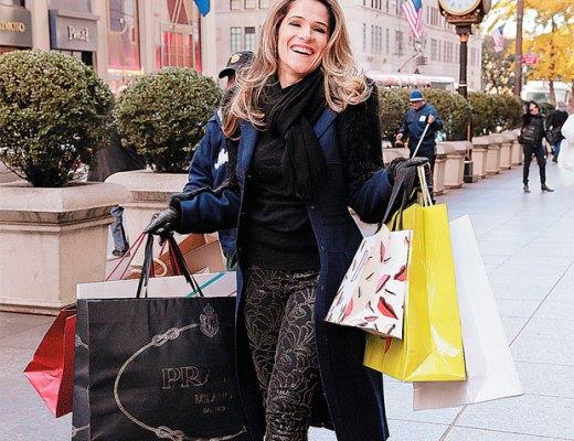 Atriz Ingrid Guimarães andando numa rua de Miami, tendo nas mãos muitas sacolas de compras. Ela veste calça escura com detalhes, e blusa preta, sobretudo escuro. Ela sorri.