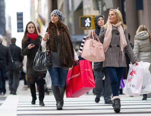 Varias mulheres andando numa rua e todas estão com muitas sacolas de compras de diversas cores.