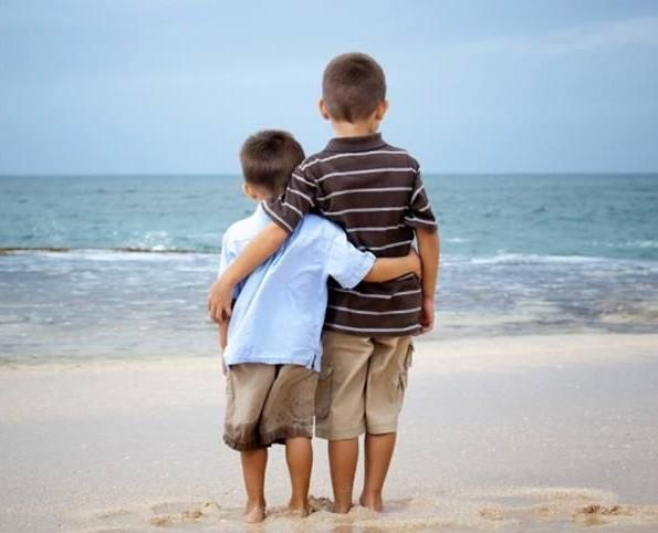 a foto mostra dosi meninos, de 7 e 5 anos abraçados olhando o mar. Eles estão com os pés na areia. a imagem transmite muito carinho entre os doi