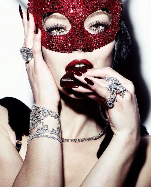 imagem de um rosto de mulher cobre os olhos com uma máscara brilhante na cor vermelha, tem suas mãos junto ao rosto, uma mão segura a máscara e a outra leva uma guloseima a boca, Ela usa um bracelete e um anel do mesmo design