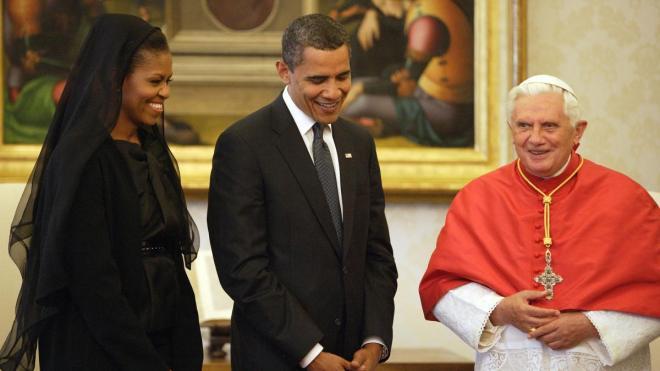 O casal Barack e Michelle Obama, em visita ao Estado do Vaticano, Itália, aparece no Salão Nobre, junto ao Papa Bento XVI. Presidente Obama veste terno na cor preta, camisa branca e gravata cinza escura. Senhora Michelle está usando um vestido, na cor preta e sobre a cabeça usa um manto suave também na cor preta