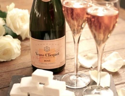 Imagem de uma mesa de madeira com tres rosas brancas a esquerda, ao centro uma garrafa de champanhe Veuve Clicquot Rosé, a frente duas taças com champanhe e junto a elas cubos brancos.