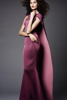 Modelo de cabelos longos e cacheados veste um vestido cor de uva também longo. O modelo é liso e'reto com mangas curtas envolvendo os ombros - delas ai uma capa longa que cai pelas costas em um movimento fluido.