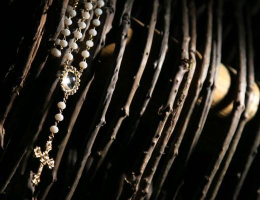 Sobre um fundo de galhos secos marrons está pendurado um terço com contas de pérolas brancas e pequenas com uma pedra sobre o crucifixo em outro delicadamente trabalhado. O material delicado do terço contrasta com o fundo escuro e rústico dos galhos secos.