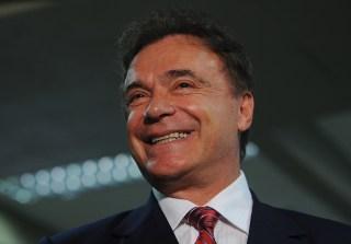 Senador Alvaro Dias, famoso pelos seus cabelos tingidos e muita plástica no rosto, usa terno escuro , camisa branca e gravata vermelha com detalhes em tons cinza claro.