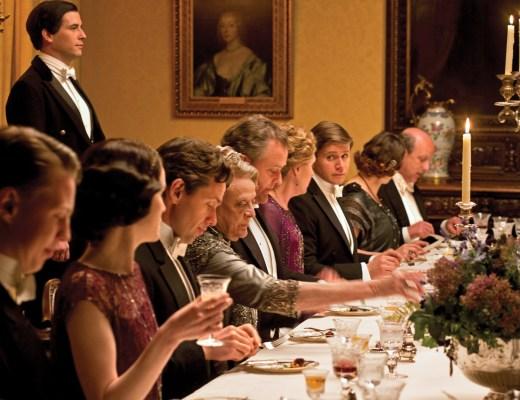 Em uma sala de jantar elegante de um lindo castelo na Inglaterra do início do século XX, os personagens da série inglesa Downton Abbey estão a mesa prontos para jantar. A mesa é oval com uma toalha creme e sobre ela taças de cristal e louça a frente de cada personagem. No centro , candelabros de cinco braços dão um toque final de requinte. O dono da Casa Lorde Crawley está ao centro da mesa e atrás dele o mordomo impecável aguarda ordens em pé, a direita e esquerda de Lorde Crawley, estão sua filha Mary e a sobrinha Rose elegantemente trajadas e a sua frente estão sua mulher, sua terceira filha e o genro, todos concentrados em uma conversa aparentemente séria.