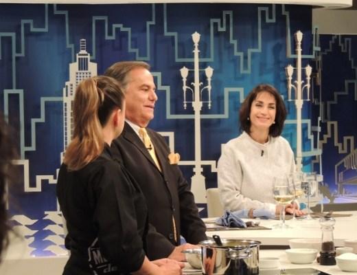 Claudia Matarazzo durante o programa do Ronnie Von . Ela veste um casaquinho sem gola numa cor clara e ele está de terno escuro , camisa branca e gravata amarela. Eles estão numa bancada aguardando um jantar. Sobre a bancada pratos e copos. Ao fundo um cenário todo azul com desenho da cidade de São Paulo.