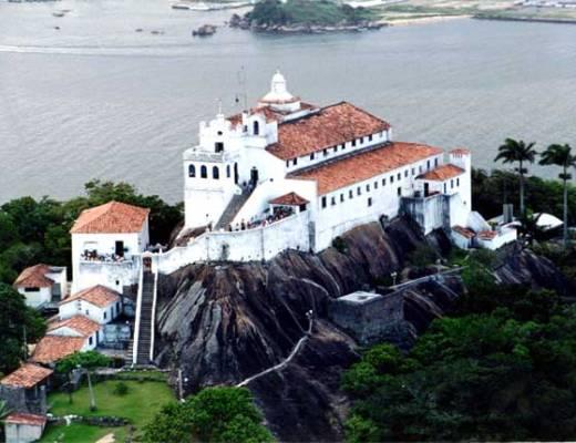 Igreja e Convento de Nossa Senhora da Penha, em Vila Velha, Espirito Santo. Na imagem , aparece toda a construção, na cor branca no topo de um monte sobre as pedras e apenas uma escada de muitos degraus.