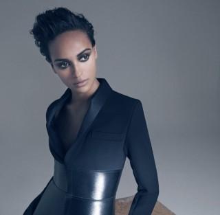 Modelo morena de coque alto usa um blazer preto de gola alta com uma faixa muito muito larga na cintura como se fosse um corpete em couro preto!