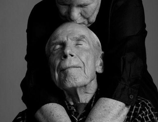 Um casal de senhores de mais de 70 anos se abraça: ele sentado e ela, de cabelos curtos brancos, veste uma malha preta, está em pé e o abraça por trás dando um beijo carinhoso na testa do parceiro que veste uma camisa xadrez. A foto é em preto e branco.