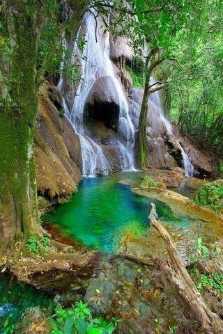 Foto de uma cachoeira junto ao Rio Bonito em Mato Grosso, , águas límpidas, esverdeadas, com mata natural densa e pedra.