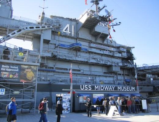 museu nos Estados Unidos, imagem de um navio de guerra ancorado para visitações , algumas pessoas na fila