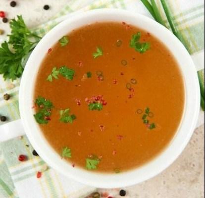a foto mostra um xicara de sopa com duas abas, vista de cima, com um caldo fino e dourado. Esta salpicado cheiro verde