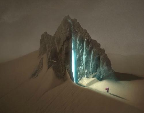 Foto de dunas de areias brancas no deserto de onde se ergue uma formação rochosa como uma grande gruta sobre a areia. Por uma abertura das paredes da gruta entra uma luz azul e forte iluminando a paisagem. Aos pés da gruta, uma figura minúscula de um beduíno com a capa esvoaçante dá idéia da grandeza da natureza.