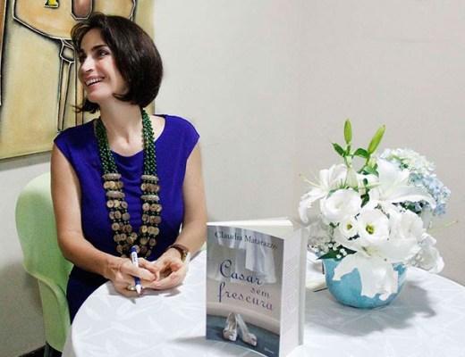 """Claudia matarazzo com um vestido azul escuro vibrante está sentada em frente a uma mesa redonda com toalha branca e com seu livro """"Casar sem Frescura""""a vista. Um vaso com folres brancas enfeita a mesa e ela sorri para alguém que está ao seu lado. O vestido é sem mangas e ela usa um colar longo e verde escuro de sementes marrons de 3 voltas . Seu cabelo é castanho escuro e está cortado rente ao queixo."""