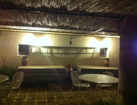 num salão externo de uma casa, numa noite, temos duas mesas junto a parede de cor branca, uma escada de pintor está fixada na parede como adorno. o teto é uma forração de pequenos gravetos.