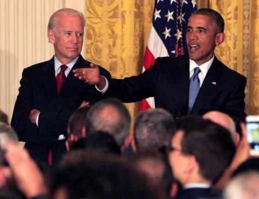 Barack Obama, Presidente dos Estados Unidos ao lado do Vice-Presidente, ambos vestindo terno escuro , camisa branca, Obama com gravata azul e o vice, com gravata na cor vermelha. Ele fala olhando para uma determinada pessoa e gesticula nessa direção, usando o branço direito. Enquanto o Vice-Presidente olha o Obama que está a sua esquerda.