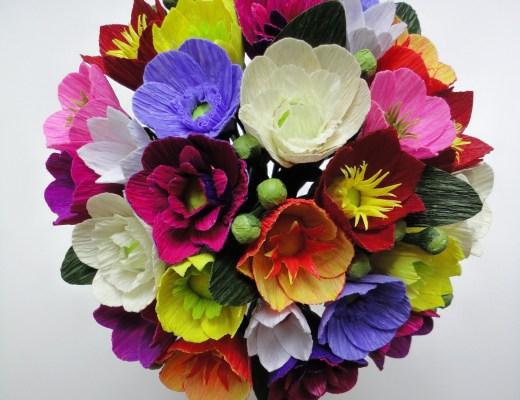 Buquê de flores muito coloridas em um mini vaso visto de cima: as flores em tons fortes de roxo, vermelho, amarelo e laranja formam um contraste alegre.