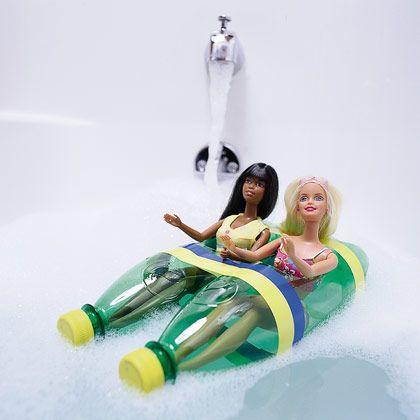 duas garrafas de pet verdes amarradas juntas como se fossem um caiaque duplo com duas bonecas Barbie como passageiras