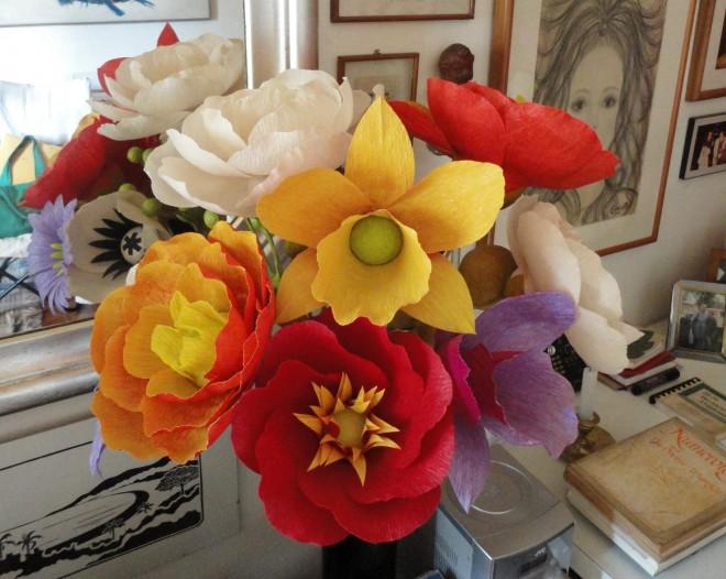 imagem de um canto de sala , com paredes com muitos quadros, em primeiro plano, um vaso com muitas flores coloridas, em tons: amarelo, branco, vermelho, roxo,