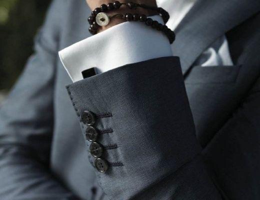 Imagem do tronco de um homem usando terno, em primeiro plano seu braço dobrado, focando no punho, camisa branca, terno na cor cinza escuro e no pulso uma corrente budista.