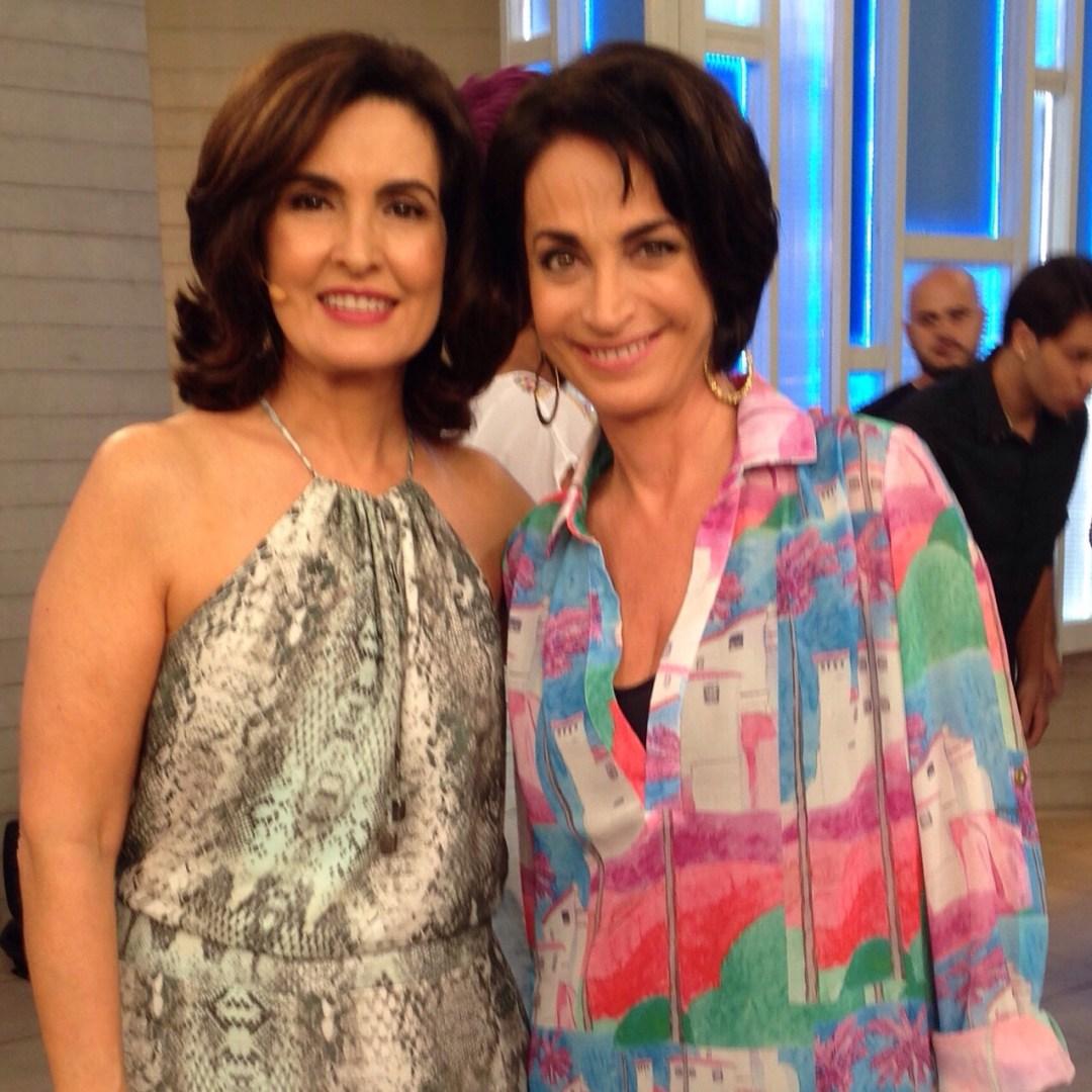 Claudia Matarazzo, usando um conjunto colorido, em vários tons de azul, rosa e vermelho. Ao seu lado, Fatima Bernardes, usando com vestido preso ao pescoço e ombro desnudos, num tecido cobra suave.