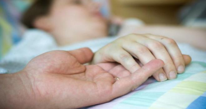 uma pessoa deitada numa cama, tem uma mão sobre um lençol com a palma para cima, com uma aliança no dedo, tem sobreposta outra mão.