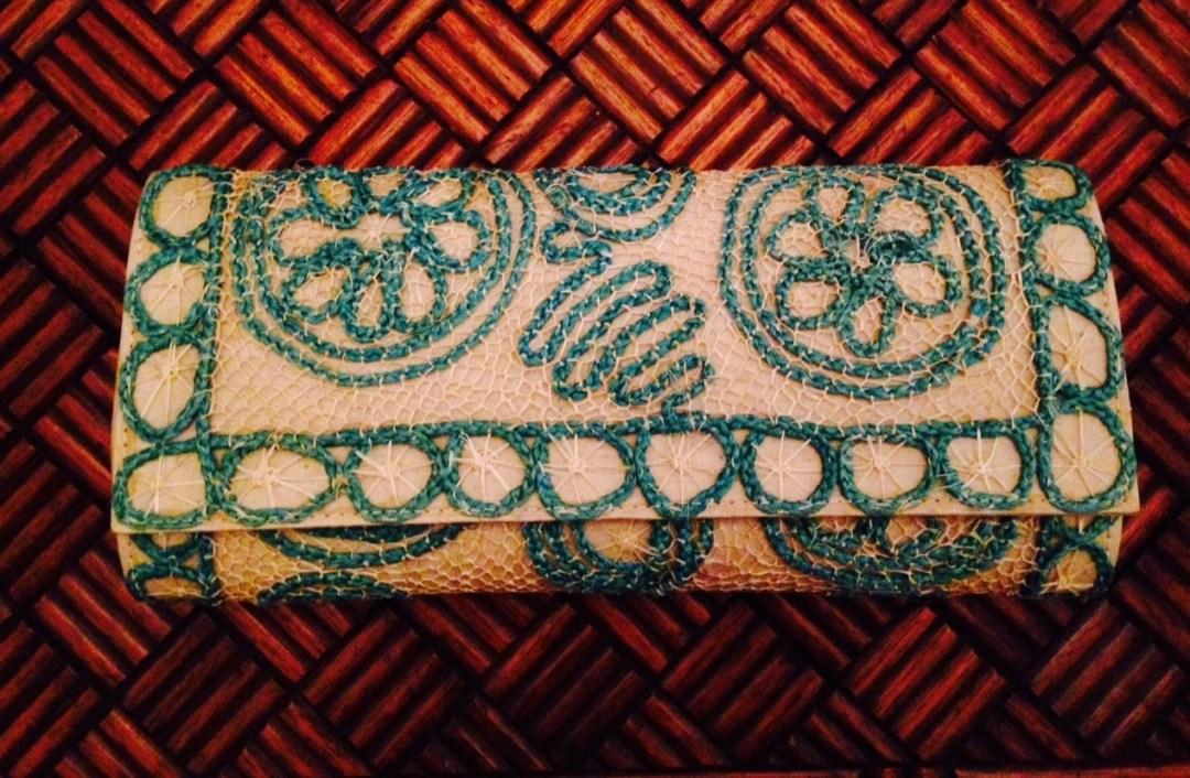 bolsa tipo carteira em palha de buriti cor creme lara delicadamente trançada de forma artesanal como uma renda, combinando com desenho floral também em palha em cor turquesa.