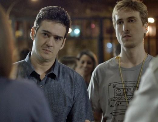 """Ator Igor Angelkorte , usando camiseta decote careca, com algumas desenhos graficos, está ao lado do ator Marcos Veras, que está usando uma camisa na cor azul , Ambos estão sérios , durante uma cena da novela """"Babilônia"""", que eles participam como amigos."""
