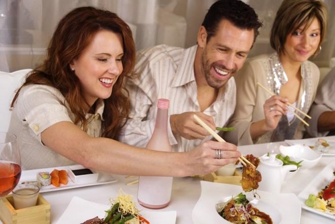 Numa mesa de jantar, um homem vestindo camisa esporte, e de barba, está entre duas senhoras , eles degustando comida japonesa .japonesa - O
