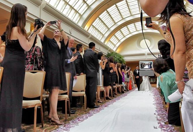 Numa igreja lotada, o padre e os noivos no altar, após a celebração do matrimônio, o padre faz uma selfie de todos.
