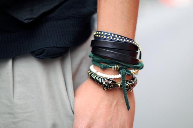 Imagem de um braço esquerdo de um homem, com muitas pulseiras , de tons escuros, em várias texturas e modelos.