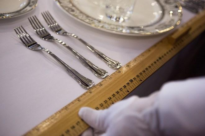 Foto em close de uma mesa colocada com uma mão de luvas brancas segurando uma régua amarela para medir a distancia entre um prato e outro.