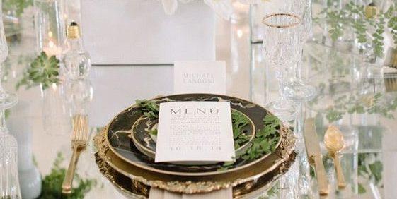 Mesa de jantar, decorada em tons de branco e amarelo, flores, copo de leite, o guardanapo está sob os pratos e se estende para o chão. O supla em tons dourados , e pratos de porcelana , cor preta e frisos dourados.