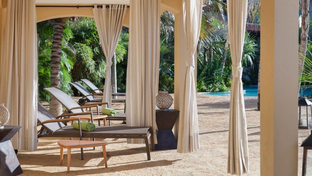 Amplo espaço junto a piscina com ambientes preservados com cortinas e cadeira de descanso