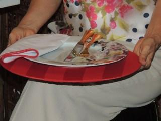 Pessoa sentada, onde não aparece o rosto e em primeiro primeiro plano, está sobre o colo um prato estampado com os talheres que estão apoiados em um apoio de prato vermelho específico para facilitar a refeição sem o auxílio da mesa.