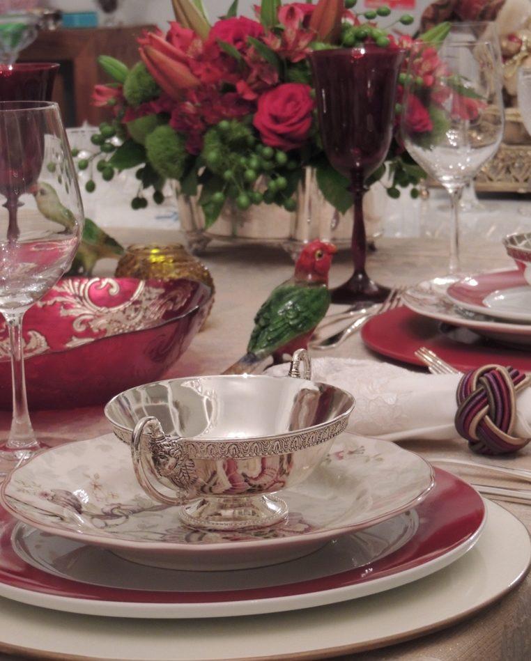 Mesa com pratos de borda vermelho escuro colocada com requinte . Sobre o prato vermelho á outro estampado nos mesmos tons onde está uma taça prateada com abas. Ao fundo um arranjo de rosas vermelhas e em primeiro plano taças de vinho transparentes e de água em tom de rubi. No centro um enfeite de passarinho de porcelana completa a decoração