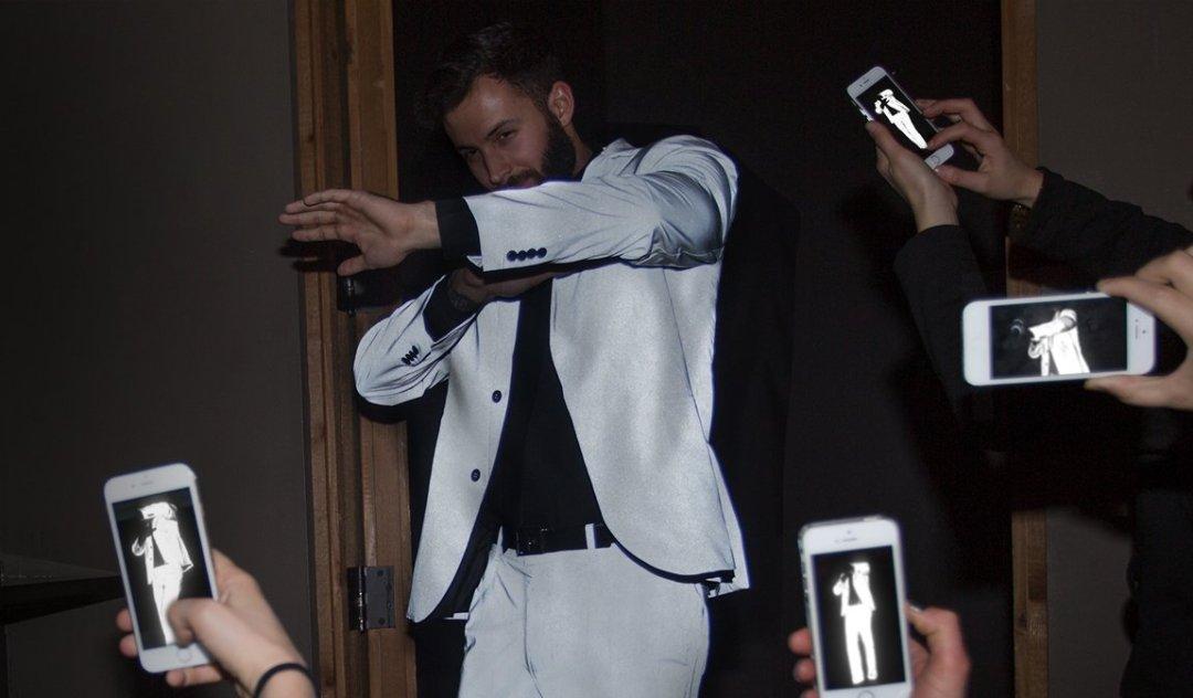 Homem usando, cabelos castanhos e barba, usa camisa social, na cor preta e terno branco. Em pé ele protege o rosto com o braço para evitar os celulares que estão a sua frente. E a foto que aparece no visto do celular não identifica seu rosto.